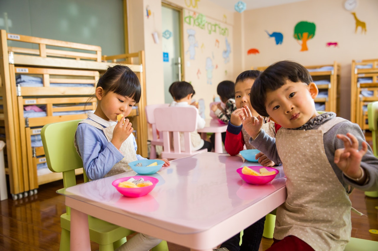 three toddler eating on white table 1001914